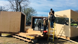Des hommes assemblent une structure de bois
