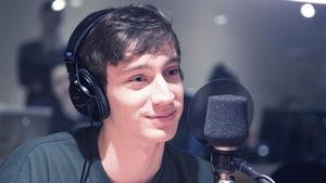 Assis derrière un micro, il porte des écouteurs sur la tête.