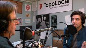 Deux hommes discutent derrière des micros dans un studio radio.