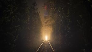 Une lumière au bout du chemin de fer qui traverse la forêt en pleine nuit.