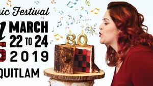 Une femme souffle une bougie du chiffre trente sur un gâteau en forme de bûche.
