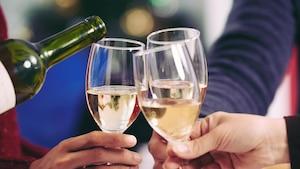 Des gens célèbrent le Nouvel An avec des coupes de vin blanc.