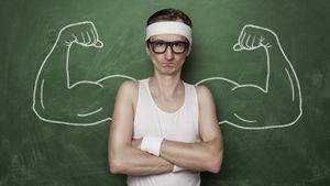 Un homme maigre aux grosses lunettes pose devant un tableau où des bras musclés sont dessinés à la craie.