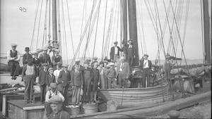 Des Madelinots posant devant les bateaux qui les mèneront vers l'Abitibi en 1942.