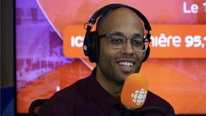 Webster derrière un micro dans un studio radio de Radio-Canada.