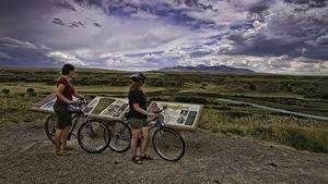 Deux cyclistes debout avec leurs vélos devant des plaques explicatives, avec une rivière, une plaine et des montagnes en arrière-plan.