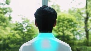 Un homme de dos porte une chemise blanche. On distingue  un cercle de couleur turquoise dans le haut du dos.