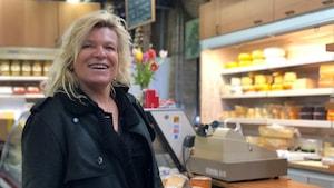 La chef française Flora Mikula debout devant un étalage de fromages