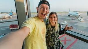 Alex Normand et MJ Lalande posent en égoportrait dans un aéroport. On aperçoit un avion en arrière-plan.