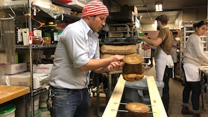 David Mattachioni suspend des panettones à l'envers pour les refroidir.