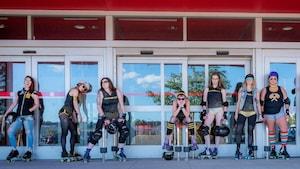 Des membres de Hammer City Roller Derby posent devant les portes d'un commerce.
