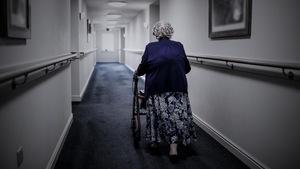 Une vieille personne de dos marche dans un couloir avec une marchette.