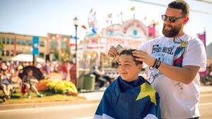 Un homme coupe les cheveux d'un garçon dans la rue.