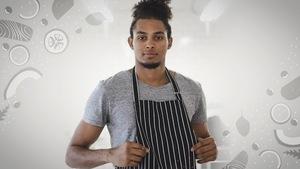 Un homme avec un tablier de cuisinier.