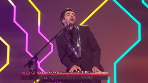 Il est debout au piano devant le public de l'émission.