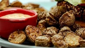 Une assiette de pommes de terre rôties aux épices à steak de Montréal, accompagnée d'une sauce Sauce McOrsini.