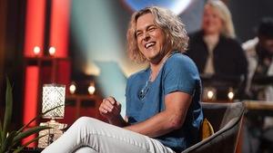 Un homme aux cheveux blonds qui rit.