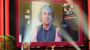 Un homme qui porte un bandeau sur la tête. Il apparaît dans un écran.