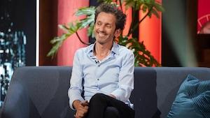 Un homme qui sourit. Il porte une chemise bleu pâle.