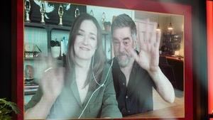 Un homme et une femme saluent de la main. Ils apparaissent dans un écran.