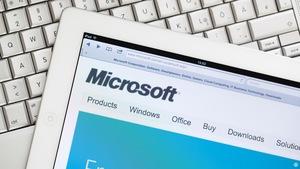Un iPad 2 affiche le site Internet de MIcrosoft, et cet ipad est déposé sur un MacBook Pro de Apple.