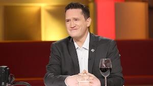 Benoit Charette porte une chemise à pois et un veston gris foncé.