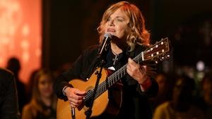 L'artiste, guitare à la main, chante.