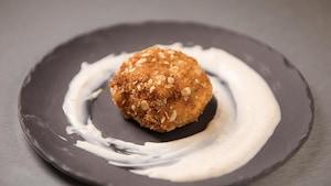 Une boule de cake de homard au centre d'une assiette avec un coulis de yogourt au citron et paprika.