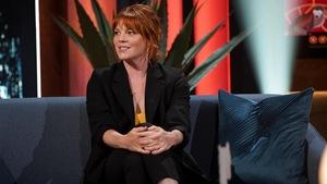 Une femme aux cheveux roux. Elle porte un veston noir.