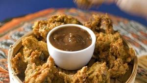 Un petit plat de sauce est posé au centre des beignets