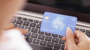 Une femme devant un clavier d'ordinateur tient une carte de crédit dans sa main.