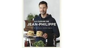 Jean-Philippe tient une assiette contenant deux burgers végétariens.