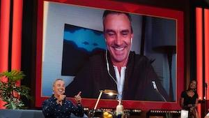 Un homme qui sourit. Il apparaît sur un écran.