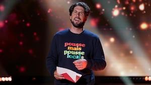 Un homme qui porte un chandail qui affiche le slogan suivant : Pousse, mais pousse local.