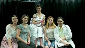 5 femmes sont sur scène. Celle du centre est attachée sur une chaise.