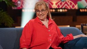 Une femme qui porte un chemisier rouge.