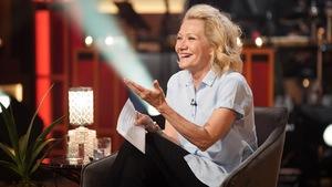 Une femme aux cheveux blonds qui rit.