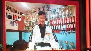 Un jeune homme qui porte un costume d'arts martiaux. Il apparaît dans un écran.