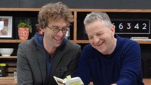 Les deux hommes qui rigolent autour d'un livre.