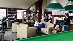 Deux femmes discutent sur un canapé. Elles sont entourées d'une équipe de télévision.