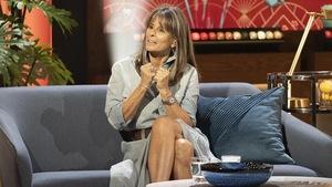 Une femme qui porte une longue robe gris-bleu.