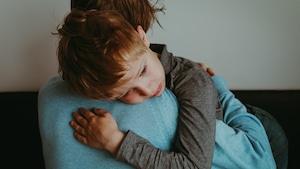 Un père porte dans ses bras son fils qui a de la peine.