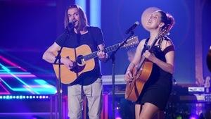 Un homme et une femme qui chantent et jouent de la guitare.