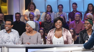 Ils sont assis à la table des invités de l'émission. Ils sourient.