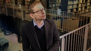 Un homme debout dans une bibliothèque.