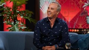 Un homme qui sourit. Il porte une chemise marine qui affiche des merlins.