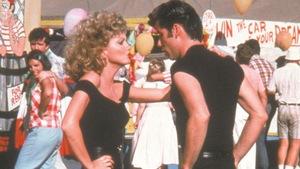 Une jeune fille (Olivia Newton-John) et un jeune homme (John Travolta) habillés tout en noir dansent.