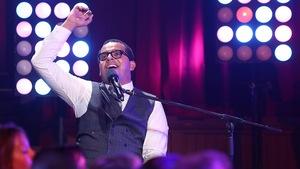 Gregory Charles devant son piano qui chante avec le bras dans les airs