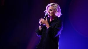 Une femme qui chante en tenant un micro dans ses mains.