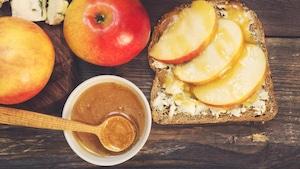 Planche de bois avec une rôtis, des pommes, du fromage et du caramel.
